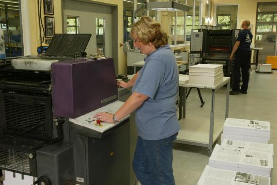 Eine Mitarbeiterin bedient eine Druckmaschine