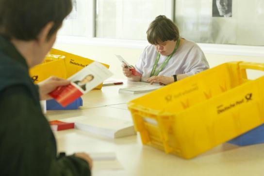 Mitarbeiter kuvertieren Broschüren im Mailing-Service