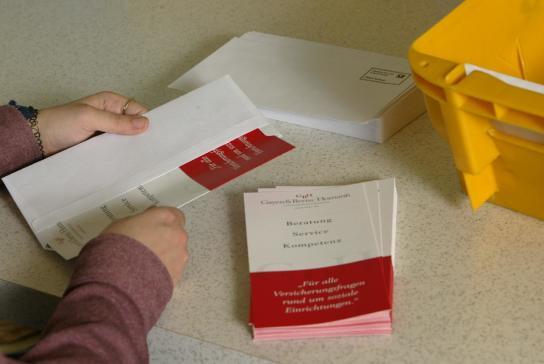 Manuelles Einkuvertieren von Flyern für den Kunden