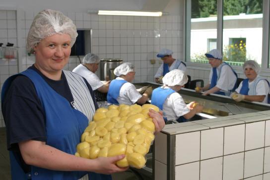 Eine Mitarbeiterin präsentiert die fertig geschälten und vakuumisierten Kartoffeln