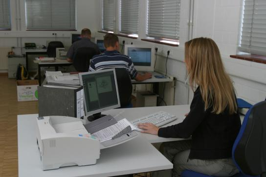 In der Datenarchivierung ist die konzentrierte Arbeit am Computer und mit Papierunterlagen des Kunden gefragt
