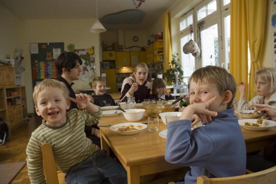 Zusammen am Tisch, Essen für alle, zwei Jungs schauen in die Kamera