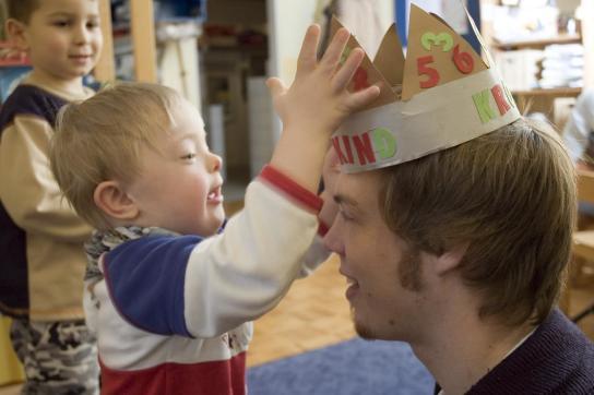 Ein Junge setzt einem Erzieher eine selbstgebastelte Krone auf