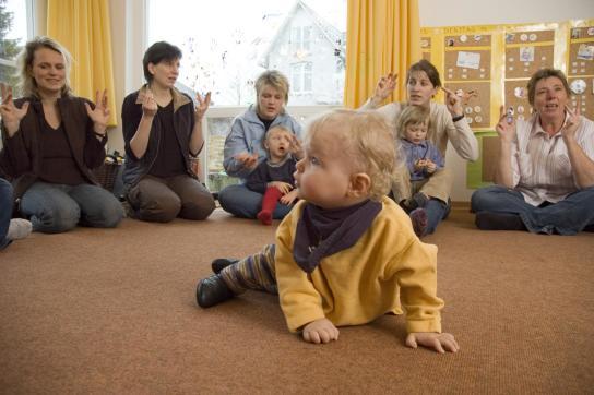 Ein Kind krabbelt inmitten des Sitzkreises