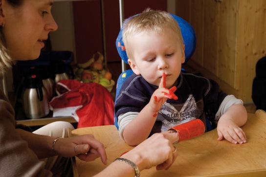 Ein Junge malt eine Papprolle mit roter FIngerfarbe an