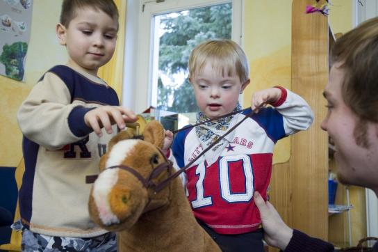 Zwei Jungs spielen mit einem großen Stoffpferd