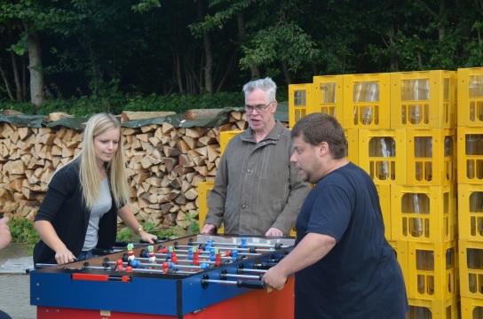 Tischkicker-Challenge vor der HOT-Pulverbeschichtung. Drei Mitarbeitende spielen die WM am Tischkicker nach.