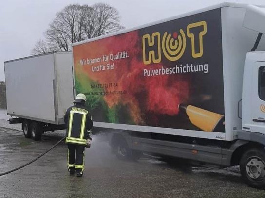 Auf dem Bild ist ein LKW der Hohenwestedter Werkstatt zu sehen. Einer der hinteren Reifen hat Feuer gefangen und wird gerade durch einen Feuerwehrmann gelöscht.