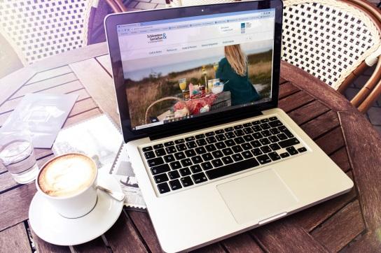 Auf dem Bild sieht man auf einem Bistro-Tisch einen Kaffee, daneben steht einen Laptop, der ein Bild der neuen Internetseite 'Schlemmen & Genießen' zeigt.