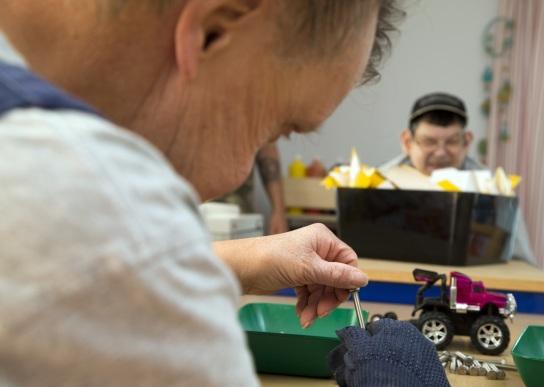 Bild Ein Mitarbeitender mit Handicap zeigt eine gr