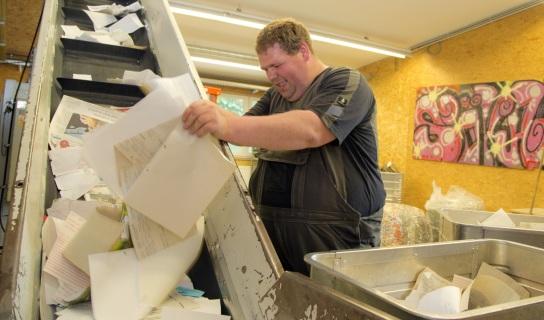Bild Ein Mitarbeiter mit Handicap legt Papiere auf das Laufband zum Schredder