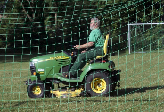 Bild Ein Mitarbeiter mit Handicap fährt mit einem Aufsitzmäher über einen Fußballplatz