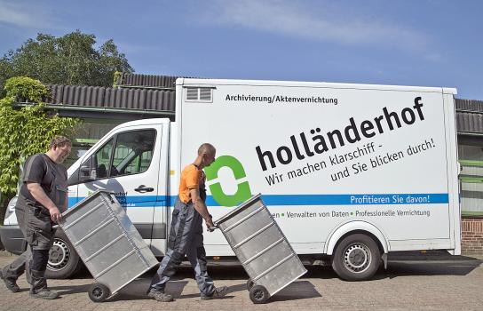 Bild Zwei Mitarbeiter mit Handicap beladen Transporter mit Sicherheitsbehältern
