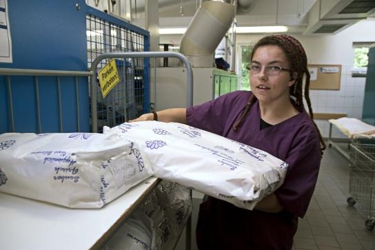 Bild Eine Mitarbeiterin mit Handicap stapelt Wäsc