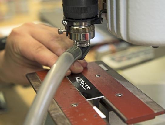 Bild Ein Schild wird an der Graviermaschine graviert