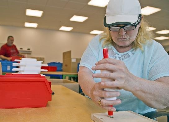 Bild Eine Mitarbeitende mit Handicap steckt ein Ku