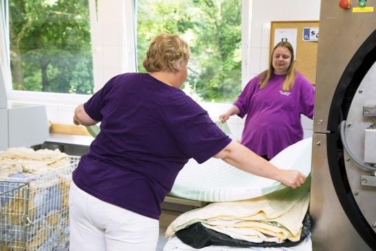 Bild Zwei Mitarbeiterinnen mit Handicap falten gro