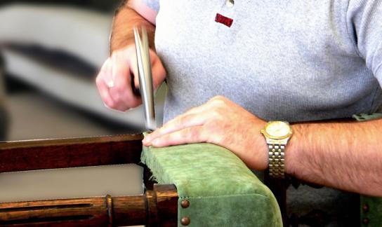Ein Mitarbeiter hämmert Nieten in einen Stuhl