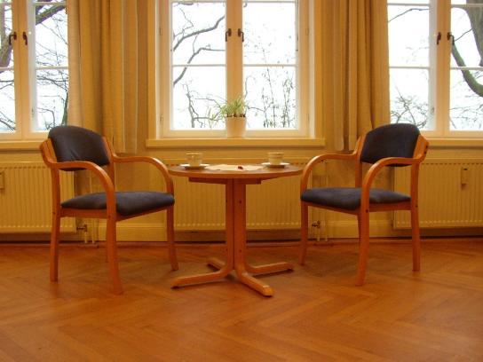 Zwei Stühle mit einem Tisch symbolisieren eine Beratungssituation in einer angenehmen Atmosphäre