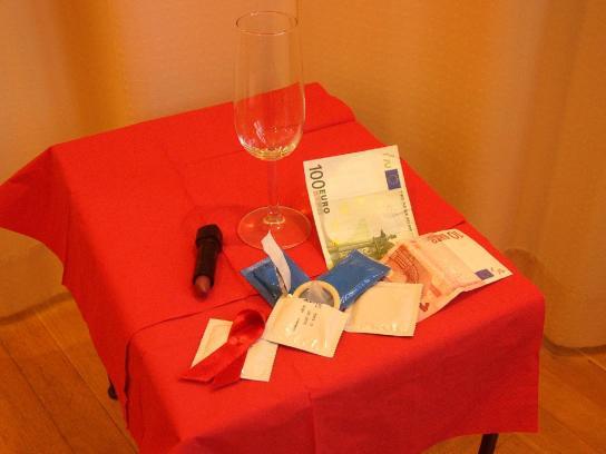 Alkohol, Geldscheine, Kondome, Gleitgel sowie eine rote Aidsschleife symbolisieren einige Aspekte von möglichen Beratungsinhalten und Themen unserer Arbeit