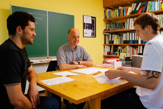 Fachkraft in unterrichtender Tätigkeit mit Berufsschülern an einem Tisch