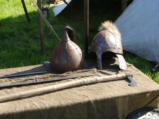 Auf einem Tisch liegen zwei Helme und Waffen aus dem Mittelalter