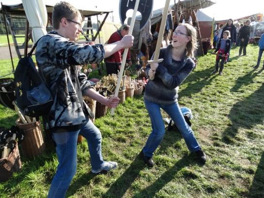 Zwei Lehrgangsteilnehmer kämpfen spielerisch mit Holzwaffen