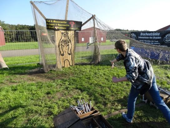 Ein Teilnehmer wirft eine Axt auf einen Bären aus Holz