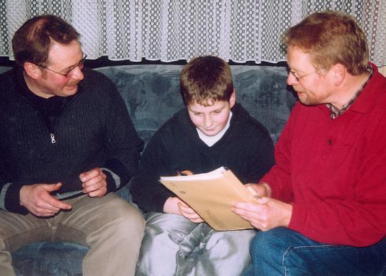 2 männliche Erwachsene sitzen auf einem Sofa mit einem Kind zwischen sich - sie diskutieren über eine Mappe