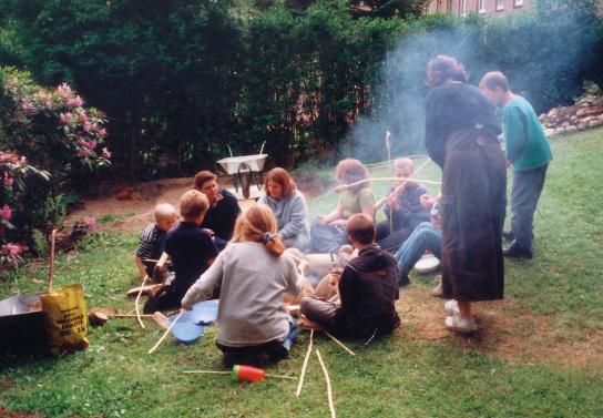 Eine Jugendgruppe sitzt um eine Feuerstelle und grillt