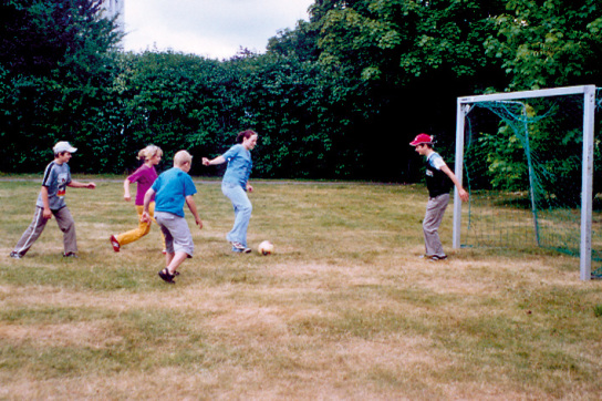 5 Kinder spielen Fussball auf ein Tor