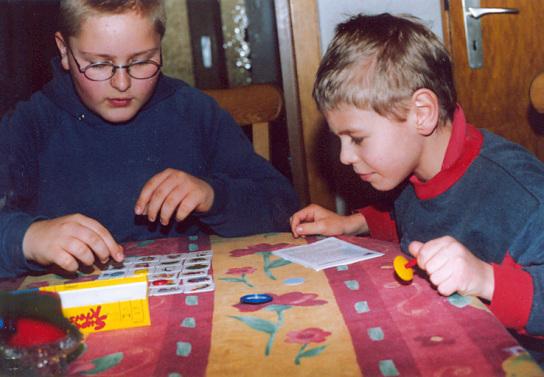 2 Kinder sitzen an einem Tisch und basteln