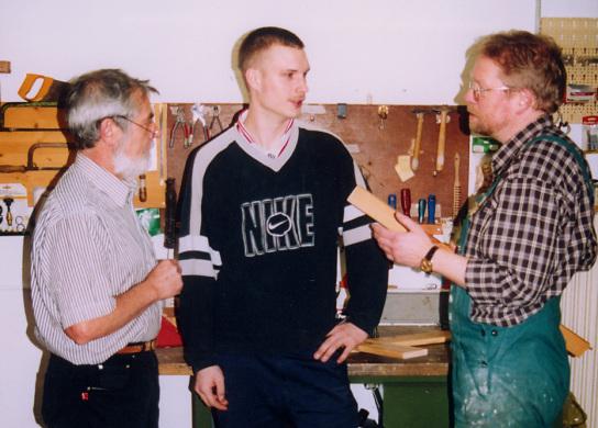 1 Teenager steht mit Betreuer in einer Werkstatt bei einem Handwerker