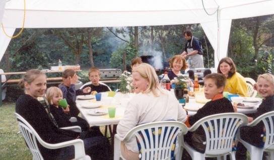 Eine Gruppe von Jugendlichen sitzt unter einem weißen Zeltdach an einem Tisch