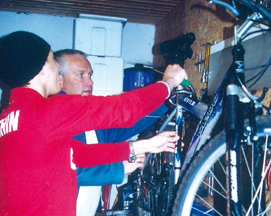 Betreuer und Jugendlicher verstauen ein Mountainbike in einer Garage