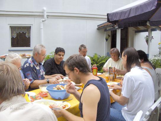 8-10 Männer sitzen um einen Tisch und nehmen eine Mahlzeit zu sich