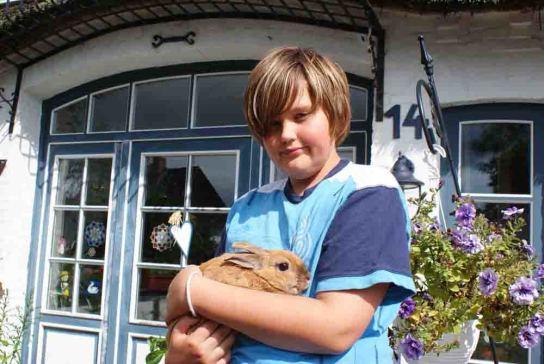Kind hält Kanienchen auf dem Arm