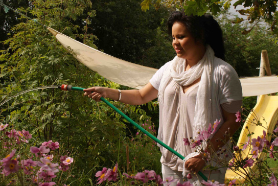 Frau bewässert Garten mit Wasserschlauch