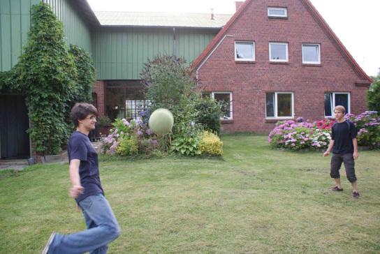 2 Teenager spielen Fussball im Garten