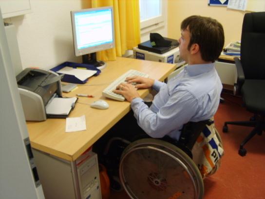Ein Rollstuhlfahrer an einem PC-Arbeitsplatz