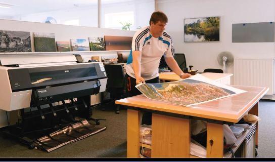 Ein Beschäftigter nimmt den Leiwanddruck aus dem Drucker.