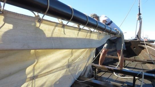 Das Segel des Wikingerschiffes wird geborgen.