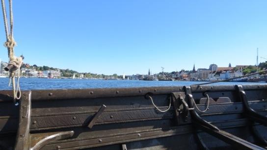 die Reling Wikingerschiff Sigyn mit Blick auf strahlend blauen Himmel, azurblauem Wasser und die Uferbebauung der Flensburger Förde.
