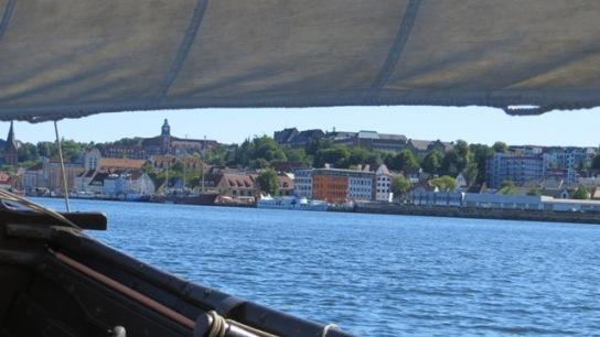 Blick durch die Luke zwischen Rahsegel und Reling auf Flensburgs Skyline
