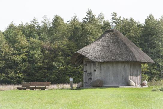 Das Bild zeigt das gut2-Quellhaus, umgeben von einer grünen Wiese und einem Wald.