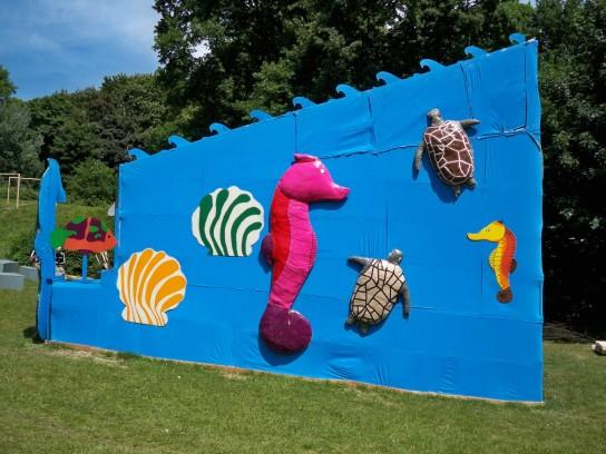 Seepferdchen, Schildkröten und Muscheln aus Pappmaché zieren die Seitenfläche der Bühne.