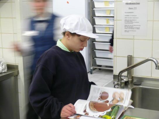 Eine Auszubildende in der Hauswirtschaft studiert ein Backbuch.