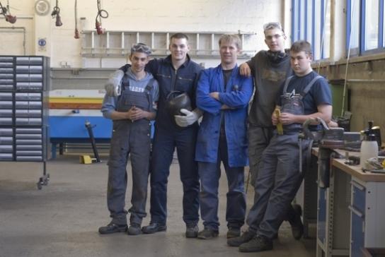 Ausbilder und Azubis in der Metallwerkstatt