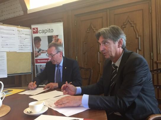 Bild: Zwei Männer in Anzügen sitzen an einem Tis