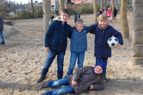 Vier Jungen auf einem Spielplatz, einer hält einen Fußball in der Hand